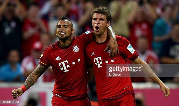 Thomas Mueller of Muenchen celebrates with Arturo Vidal after scoring his teams fourth goal during the Bundesliga match between FC Bayern Muenchen...