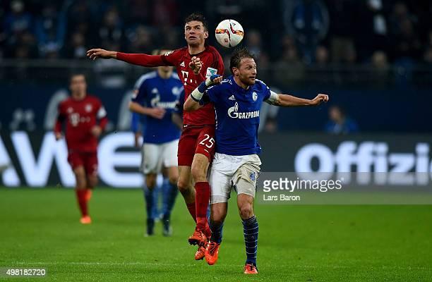 Thomas Mueller of Muenchen challenges Benedikt Hoewedes of Schalke during the Bundesliga match between FC Schalke 04 and FC Bayern Muenchen at...