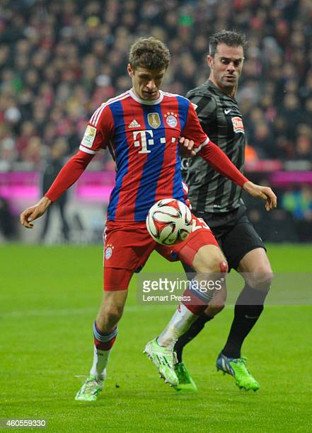 Thomas Mueller of Muenchen challenges Marc Torrejon of Freiburg during the Bundesliga match between FC Bayern Muenchen and SC Freiburg at Allianz...