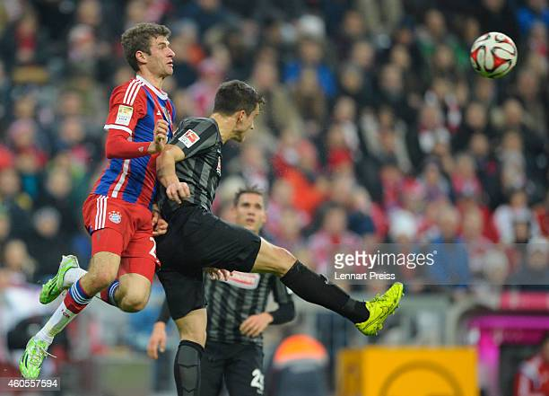 Thomas Mueller of Muenchen challenges MarcOliver Kempf of Freiburg during the Bundesliga match between FC Bayern Muenchen and SC Freiburg at Allianz...
