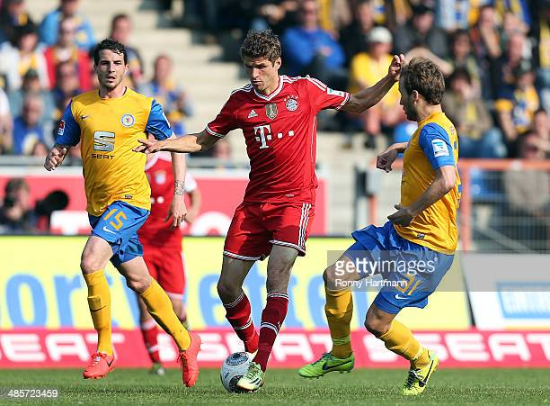 Thomas Mueller of Muenchen competes with Norman Theuerkauf and Marc Pfitzner of Braunschweig during the Bundesliga match between Eintracht...