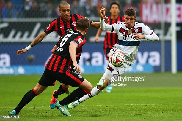 Thomas Mueller of Muenchen is challenged by Bamba Anderson and Bastian Oczipka of Frankfurt during the Bundesliga match between Eintracht Frankfurt...