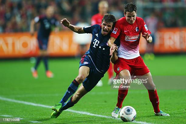 Thomas Mueller of Muenchen is challenged by Christian Guenter of Freiburg during the Bundesliga match between SC Freiburg and FC Bayern Muenchen at...