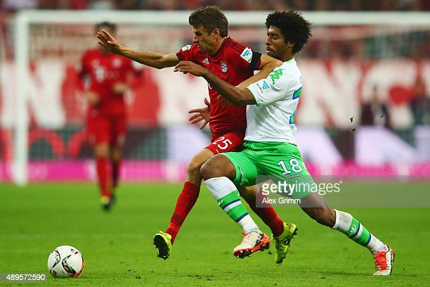 Thomas Mueller of Muenchen is challenged by Dante of Wolfsburg during the Bundesliga match between FC Bayern Muenchen and VfL Wolfsburg at Allianz...