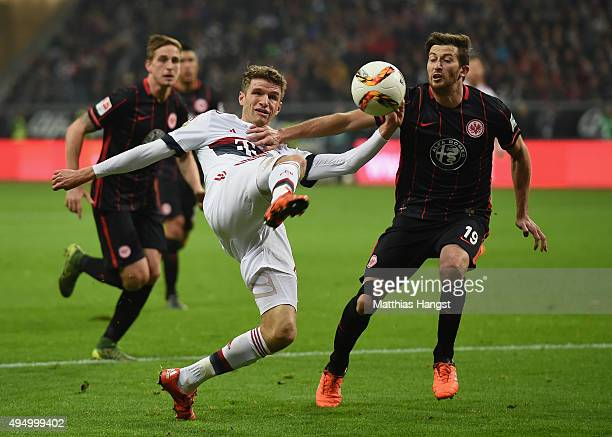 Thomas Mueller of Muenchen is challenged by David Abraham of Frankfurt during the Bundesliga match between Eintracht Frankfurt and FC Bayern Muenchen...