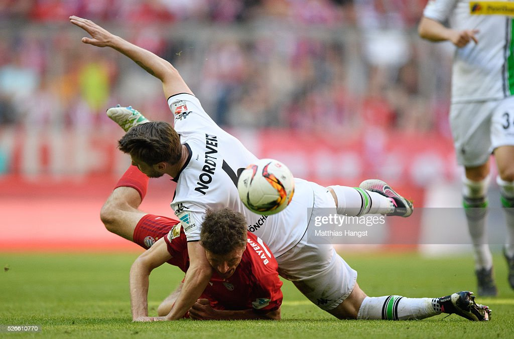 Thomas Mueller of Muenchen is challenged by Havard Nordtveit of Gladbach during the Bundesliga match between FC Bayern Muenchen and Borussia Moenchengladbach at Allianz Arena on April 30, 2016 in Munich, Germany.