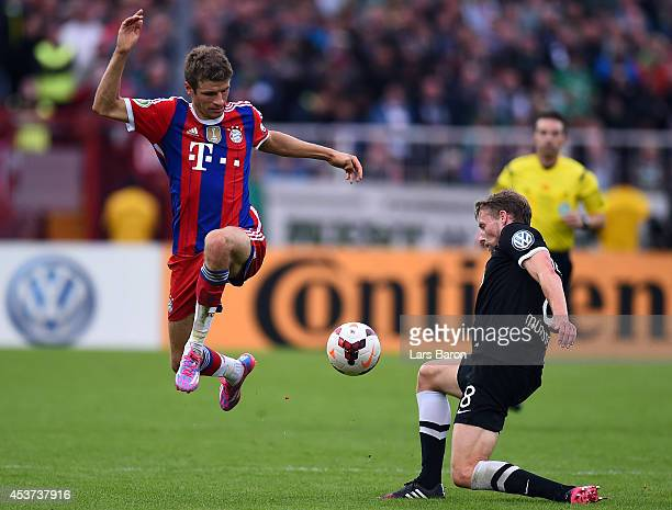 Thomas Mueller of Muenchen is challenged by Marc Heitmeier of Muenster during the DFB Cup first round match between Preussen Muenster and FC Bayern...