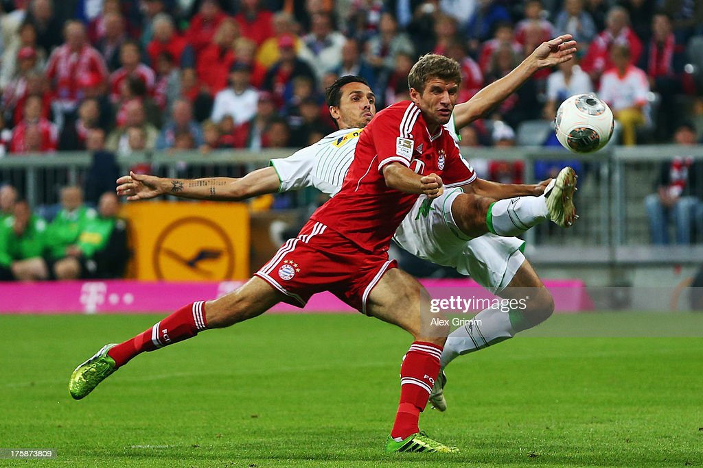 Thomas Mueller of Muenchen is challenged by Martin Stranzl of Moenchengladbach during the Bundesliga match between Bayern Muenchen and Borussia...