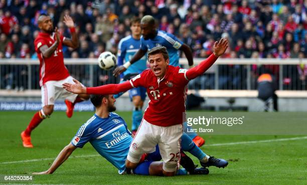 Thomas Mueller of Muenchen is tackled by Mergim Mavraj of Hamburg battle for the ball during the Bundesliga match between Bayern Muenchen and...