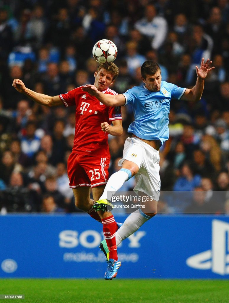 <a gi-track='captionPersonalityLinkClicked' href=/galleries/search?phrase=Thomas+Mueller&family=editorial&specificpeople=5842906 ng-click='$event.stopPropagation()'>Thomas Mueller</a> of Muenchen jumps for a header with Matija Nastasic of Manchester City during the UEFA Champions League Group D match between Manchester City and FC Bayern Muenchen at Etihad Stadium on October 2, 2013 in Manchester, England.