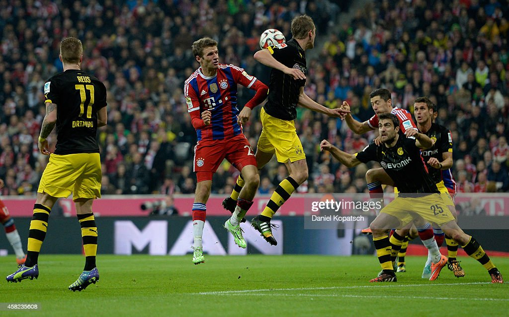 Thomas Mueller of Muenchen jumps for a header with Sven Bender of Dortmund during the Bundesliga match between FC Bayern Muenchen and Borussia...