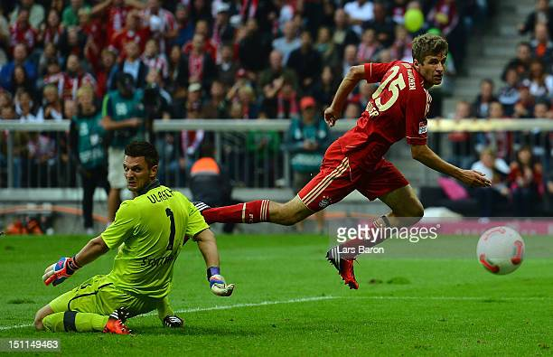 Thomas Mueller of Muenchen scores his teams first goal against Sven Ulreich of Stuttgart during the Bundesliga match between FC Bayern Muenchen and...