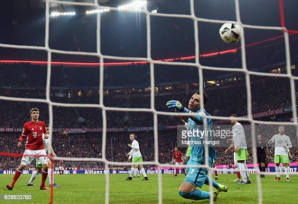 Thomas Mueller of Muenchen scores his team's fourth goal past goalkeeper Diego Benaglio of Wolfsburg during the Bundesliga match between Bayern...