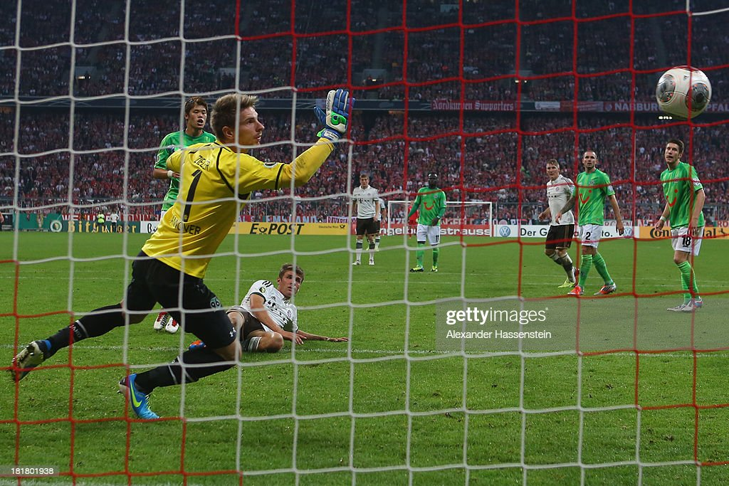 Thomas Mueller of Muenchen scores the 3rd team goal against Hiroki Sakai of Hannover and his keeper RonRobert Zieler during the DFB Cup match between...