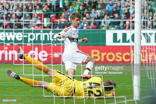 Thomas Mueller of Muenchen scores the opening goal against Felix Wiedwald keeper of Bremen during the Bundesliga match between SV Werder Bremen and...