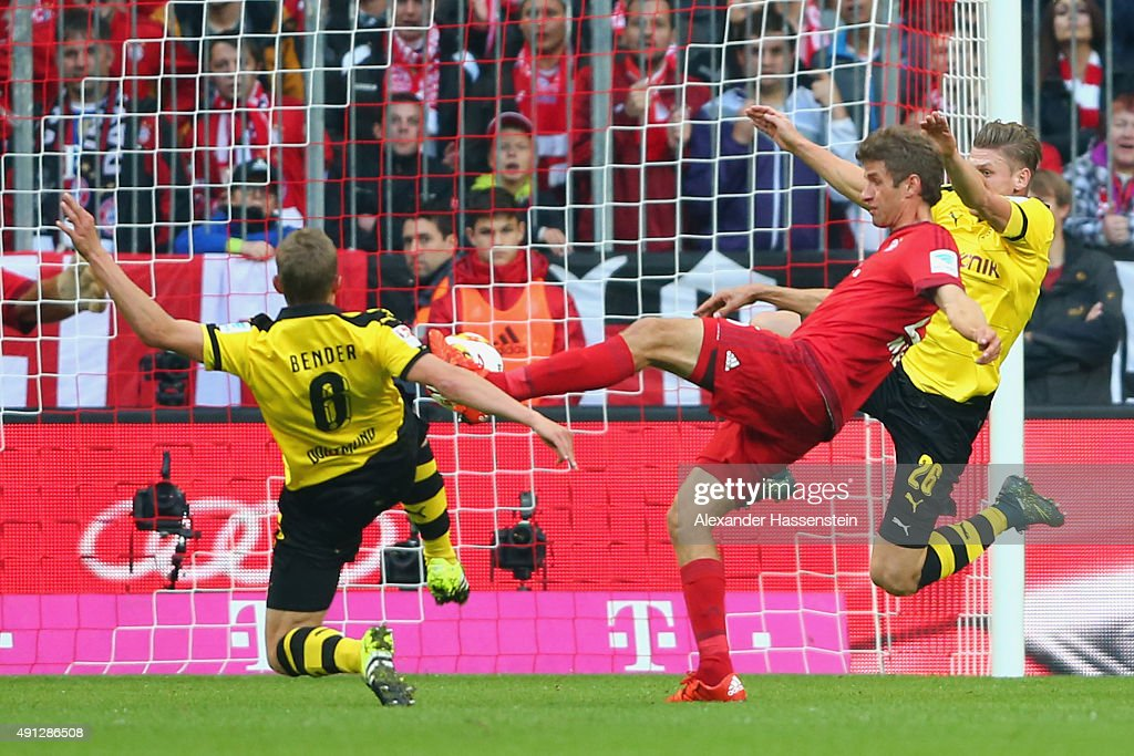 Thomas Mueller of Muenchen scores the opening goal against Sven Bender of Dortmund and his team mate Lukasz Piszczek during the Bundesliga match...