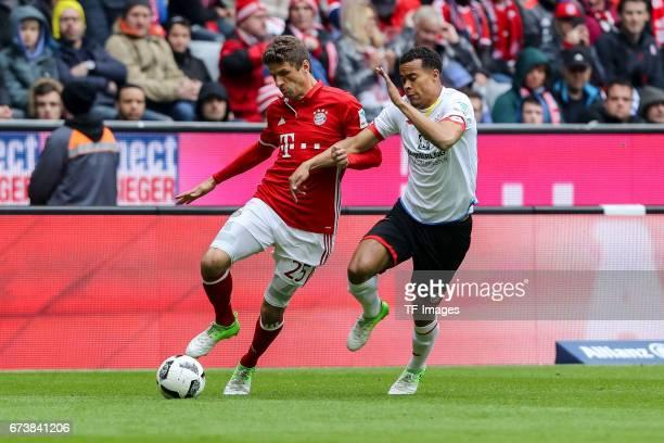 Thomas Mueller of Munich and Robin Kwamina Quaison of Mainz battle for the ball during the Bundesliga match between Bayern Muenchen and 1 FSV Mainz...