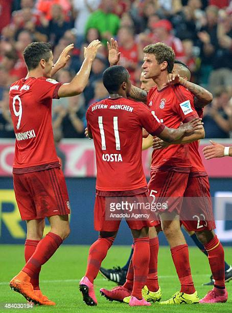 Thomas Mueller of Munich celebrates with his teammates Robert Lewandowski and Douglas Costa after scoring a goal during the German Bundesliga soccer...