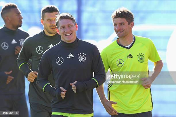 Thomas Mueller of the German national team runs with his team mate Bastian Schweinstieger during a training session at Bayern Muenchen's trainings...