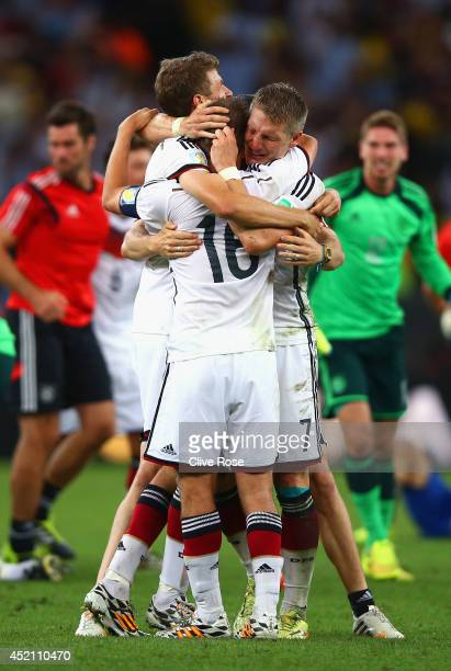 Thomas Mueller Philipp Lahm and Bastian Schweinsteiger of Germany celebrate after defeating Argentina 10 in extra time during the 2014 FIFA World Cup...