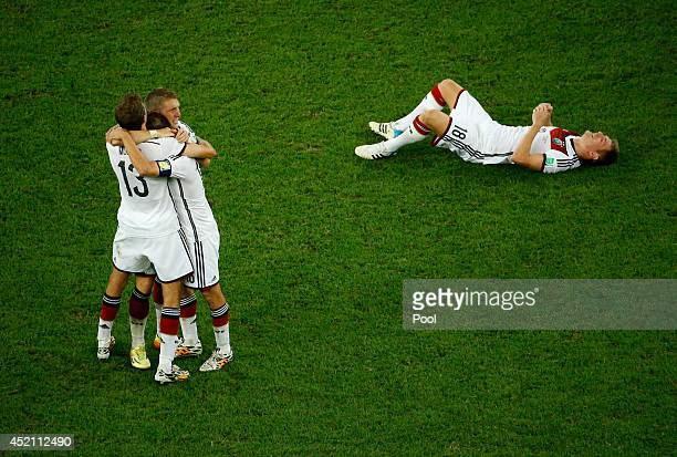 Thomas Mueller Philipp Lahm Bastian Schweinsteiger and Toni Kroos of Germany celebrate after defeating Argentina 10 in extra time during the 2014...