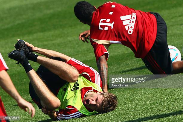 Thomas Mueller reacts after being hit by Luiz Gustavo during a training session of Bayern Muenchen at the ASPIRE Academy for Sports Excellence on...