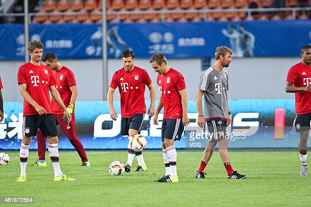 Thomas Mueller Xabi Alonso and Philipp Lahm of FC Bayern Muenchen warm up prior to the international friendly match between Guangzhou Evergrande and...