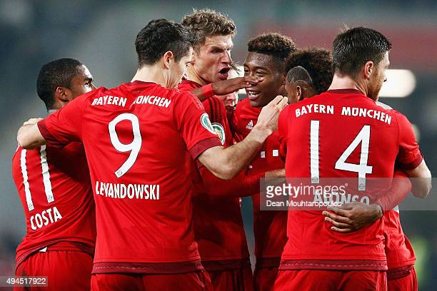 Thomas Muller of Bayern Muenchen celebrates scoring his teams second goal of the game with teammates during the DFB Cup match between VfL Wolfsburg...