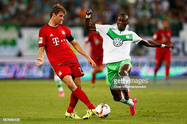 Thomas Muller of Bayern Muenchen paases the ball in front of Josuha Guilavogui of VfL Wolfsburg during the DFL Supercup match between VfL Wolfsburg...