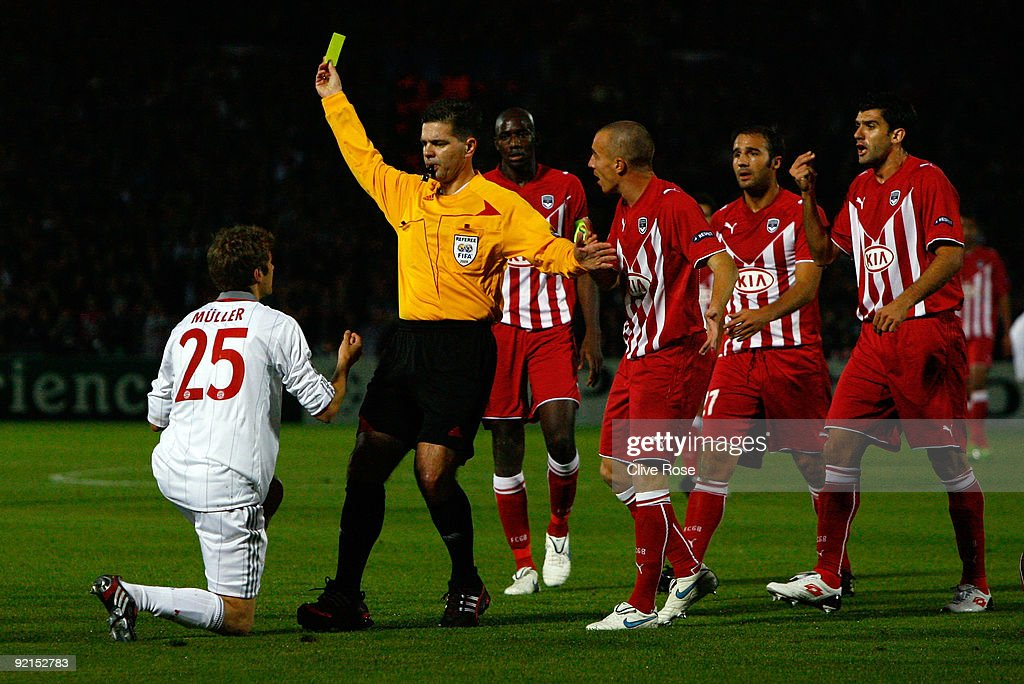 Thomas Muller of Bayern Muenchen receives his first yellow card from Referee Terje Hauge during the UEFA Champions League Group A match between...
