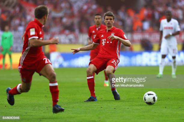 Thomas Muller of Bayern Munich passes to team mate Philipp Lahm during the Bundesliga match between 1 FC Koeln and Bayern Muenchen at...