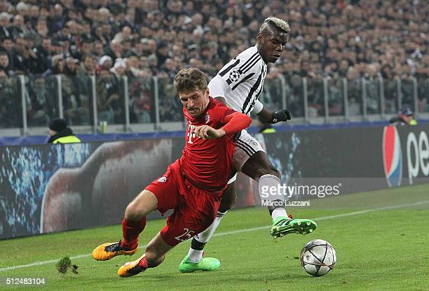 Thomas Muller of FC Bayern Muenchen competes for the ball with Paul Pogba of Juventus FC during the UEFA Champions League Round of 16 first leg match...