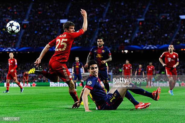 Thomas Muller of FC Bayern Muenchen duels for the ball with Marc Bartra of FC Barcelona during the UEFA Champions League semifinal second leg match...