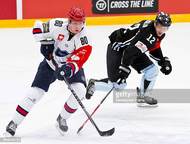 Thomas Nykoop of IFK Helsinki takes the puck past the challenge of Patrick Asselin of Sonderjyske Vojens during the Champions Hockey League group...