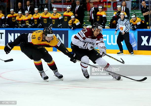 Thomas Oppenheimer of Germany and Gunars Skvorcovs of Latvia battle for the puck during the IIHF World Championship group A match between Czech...