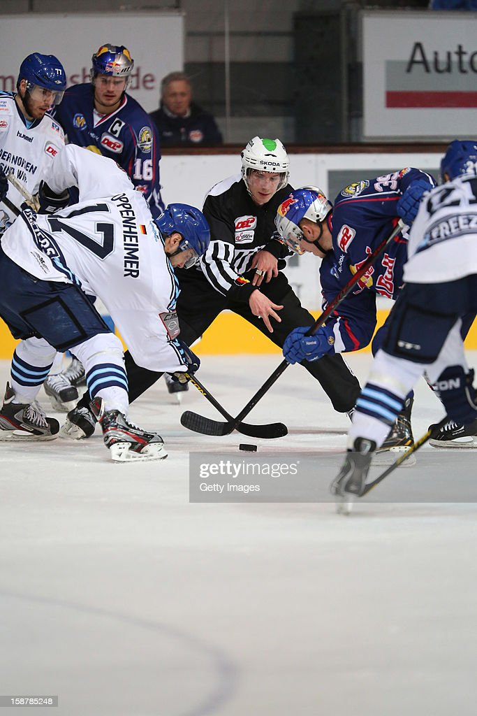 Thomas Oppenheimer (L) of Hamburg Freezers in action with Jason Ulmer of EHC Red Bull Munich re-start the game during the DEL ice hockey game between Red Bull Munich and Hamburg Freezers at Olympia Eishalle on December 28, 2012 in Munich, Germany.