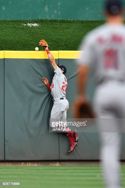 Thomas Pham of the St Louis Cardinals is unable to make the catch as a ball hit by Adam Duvall of the Cincinnati Reds bounces off the top of the...