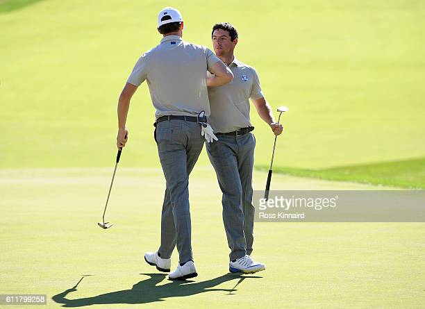 Thomas Pieters and Rory McIlroy of Europe react after winning their match on the 16th green during morning foursome matches of the 2016 Ryder Cup at...