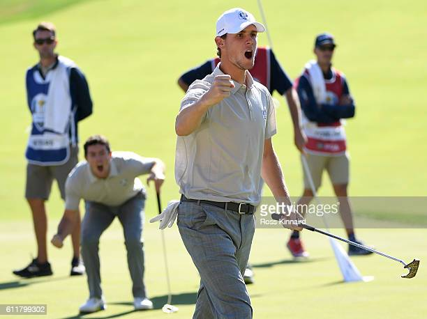 Thomas Pieters of Europe reacts after a putt on the 16th green to win the match as Rory McIlroy looks on during morning foursome matches of the 2016...