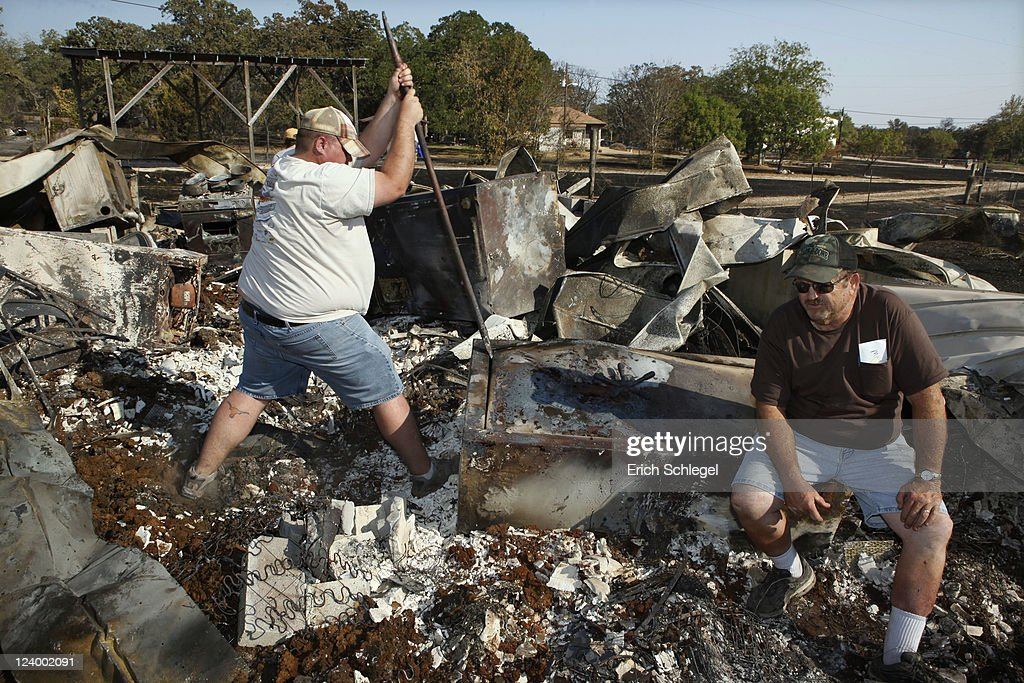 Thomas Polly tries to pry open a fireproof gun safe with his father Louie Polly counter balancing in the rubble of their burned house in a subdivision, September 7, 2011 near Bastrop, Texas. Several large wildfires have been devastating Bastrop County for the last three days, but are now 30 percent contained, according to the Texas Forest Service.