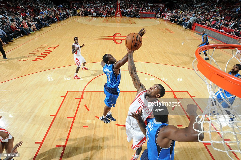 Thomas Robinson #0 of the Houston Rockets grabs a rebound against <a gi-track='captionPersonalityLinkClicked' href=/galleries/search?phrase=Rodrigue+Beaubois&family=editorial&specificpeople=5299423 ng-click='$event.stopPropagation()'>Rodrigue Beaubois</a> #3 and <a gi-track='captionPersonalityLinkClicked' href=/galleries/search?phrase=Bernard+James&family=editorial&specificpeople=7387529 ng-click='$event.stopPropagation()'>Bernard James</a> #5 of the Dallas Mavericks on March 3, 2013 at the Toyota Center in Houston, Texas.