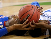 Thomas Robinson of the Kansas Jayhawks and Michael KiddGilchrist of the Kentucky Wildcats lay on the court with the ball between them in the first...