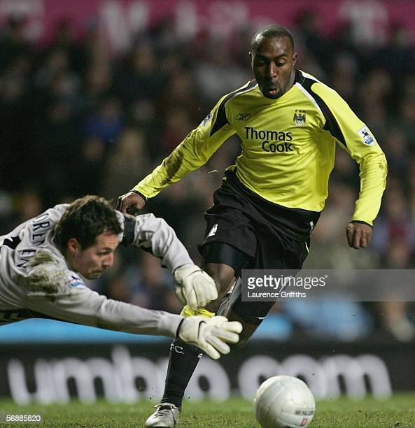Thomas Sorensen of Aston Villa dives to make a save at the feet of Darius Vassell of Manchester City during the FA Cup fifth round match between...
