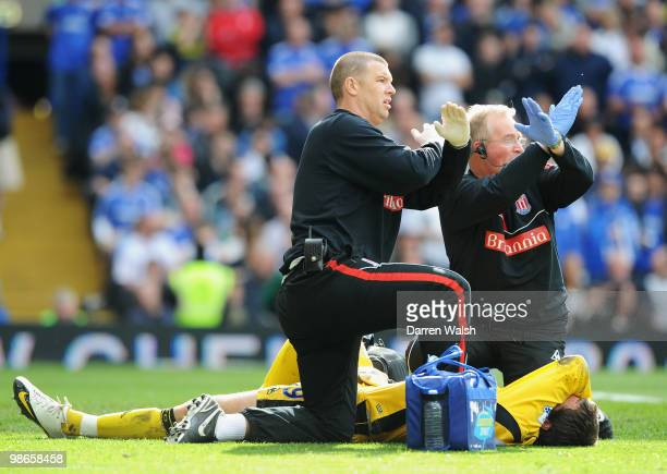 Thomas Sorensen of Stoke City is given treatment during the Barclays Premier League match between Chelsea and Stoke City at Stamford Bridge on April...