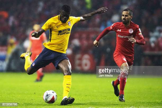 Thomas Teye Partey of Atletico de Madrid shoots the ball as Rodrigo Lopez of Toluca defends during a friendly match between Toluca and Atletico de...