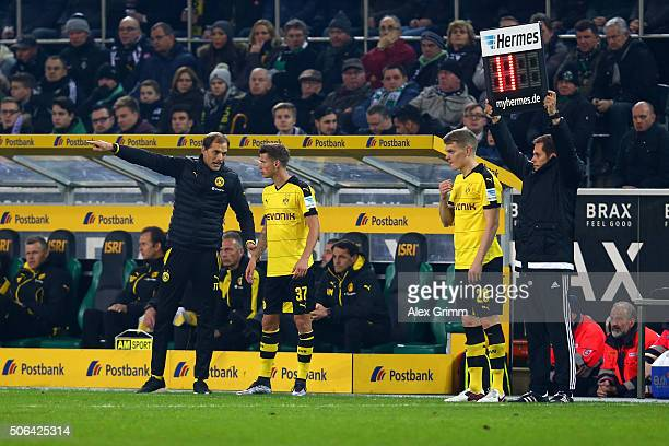 Thomas Tuchel manager of Borussia Dortmund talks to substitute Eric Durm of Borussia Dortmund as Matthias Ginter looks on during the Bundesliga match...