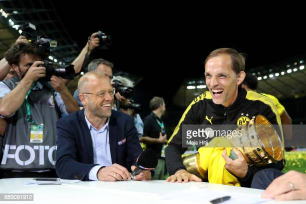 Thomas Tuchel of Dortmund laughs while holding the trophy after winning the DFB Cup final match between Eintracht Frankfurt and Borussia Dortmund at...