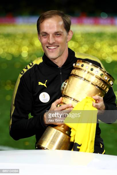 Thomas Tuchel of Dortmund smiles while holding the trophy after winning the DFB Cup final match between Eintracht Frankfurt and Borussia Dortmund at...