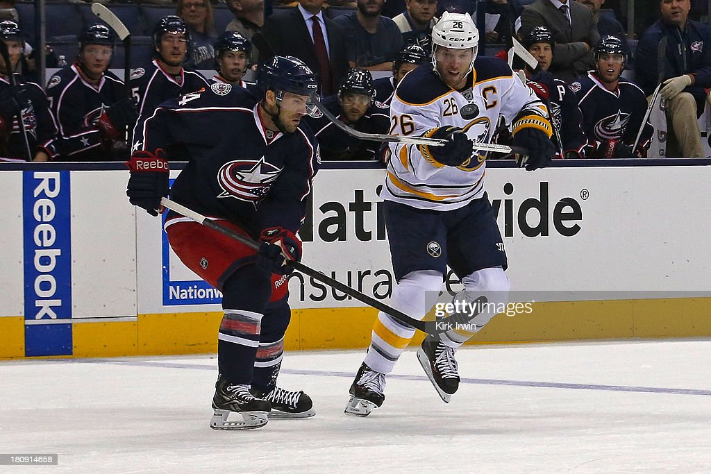 Thomas Vanek #26 of the Buffalo Sabres bounces the puck on his stick while attempting to keep control of the puck away from Andrew Joudrey #34 of the Columbus Blue Jackets on September, 2013 at Nationwide Arena in Columbus, Ohio. Buffalo defeated Columbus 3-1.