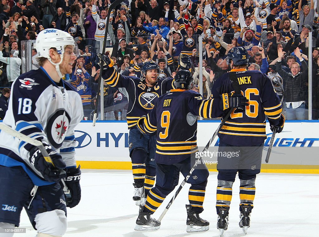 <a gi-track='captionPersonalityLinkClicked' href=/galleries/search?phrase=Thomas+Vanek&family=editorial&specificpeople=570606 ng-click='$event.stopPropagation()'>Thomas Vanek</a> #26 of the Buffalo Sabres celebrates his game winning overtime goal with teammates <a gi-track='captionPersonalityLinkClicked' href=/galleries/search?phrase=Jason+Pominville&family=editorial&specificpeople=570525 ng-click='$event.stopPropagation()'>Jason Pominville</a> #29 and <a gi-track='captionPersonalityLinkClicked' href=/galleries/search?phrase=Derek+Roy&family=editorial&specificpeople=203272 ng-click='$event.stopPropagation()'>Derek Roy</a> #9 as Bryan Little #18 of the Winnipeg Jets skates by at First Niagara Center on November 8, 2011 in Buffalo, New York.